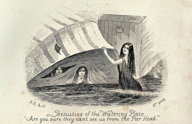 A woman holding up a canopy attached to a bathing machine two women are peering out. Wood engraving. Wellcome Collection. CC BY e1563313913792